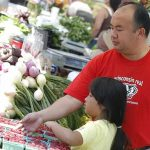 Phil Yang, an adviser and minority and disadvantaged coordinator in the School of Human Ecology, spends his Saturdays working at his family's farm stand at the Dane County Farmers' Market in downtown Madison. For 14 years, Yang's parents, Mee Xiong and Shoua Yang, have been selling fruits and vegetables that they grow on five acres of land in Oregon, Wis. Yang's daughter, Ashley, 6, also helps. © UW-Madison University Communications 608-262-0067 Photo by: Michael Forster Rothbart Date:  7/06    File#:  D100 digital camera frame 1