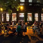 People socialize at the Memorial Union Terrace at the University of Wisconsin-Madison during a summer night on July 26, 2014. In the background are illuminated windows for the Memorial Union's Rathskeller. (Photo by Jeff Miller/UW-Madison)
